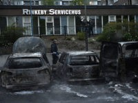 A police officers passes the scene of cars gutted by fire in the Stockholm suburb of Rinkeby after youths rioted in several different suburbs around Stockholm, Sweden for a fourth consecutive night on May 23, 2013. In the suburb of Husby, where the riots began on Sunday in response to the fatal police shooting of a 69-year-old machete-wielding man, 80 percent of residents are immigrants and the unrest has highlighted Sweden's failure to integrate swathes of its immigrant population, but in this small, consensus-driven country, there was little agreement on how to solve the problem.  AFP PHOTO / JONATHAN NACKSTRAND        (Photo credit should read JONATHAN NACKSTRAND/AFP/Getty Images)