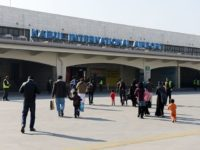 Passengers of a commercial airliner walk towards the main building of Kabul's Khwaja Rawash International airport in Kabul on December 26, 2013, after their disembarkation from an aircraft. The airport initially built in the 1960's has been upgraded in the last decade and it is surrounded by national and foreign …