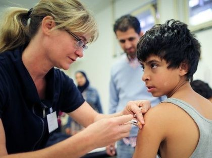 A young Syrian refugee from Damascus gets a vaccination from doctor Susanne Eipper (L) at the State Office of Health and Social Affairs (LAGeSo) in Berlin on October 1, 2015. A record 270,000 to 280,000 refugees arrived in Germany in September, more than the total for 2014. The sudden surge …