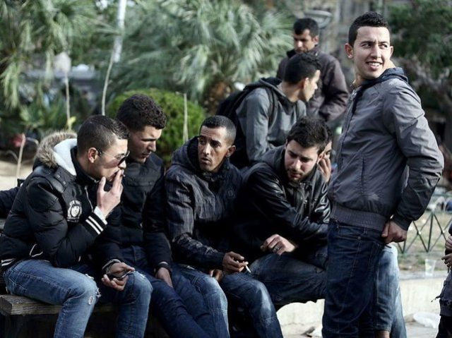 Migrants men sit on a bench on March 3, 2016 at the Victoria square in central Athens, where hundreds of migrants and refugees stay temporarily. Athens said on March 3, 2016 it now had nearly 32,000 migrants on its territory, after Austria and Balkan states began restricting entries, creating a …