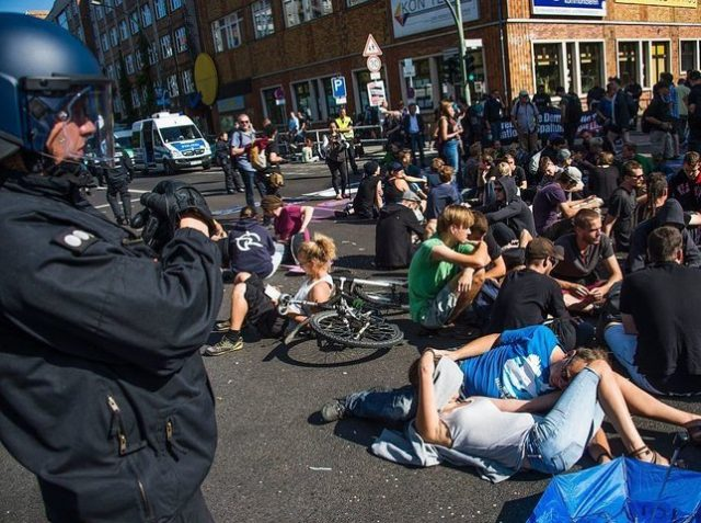 Activists from the Blockupy movement stage a sit down in front of the ministry for works and pension in Berlin on September 2, 2016. Hundreds of demonstrators walked from two locations in central Berlin converging at the ministry in Berlin's Wilhelm strasse to protest the German governments asylum policy. / …