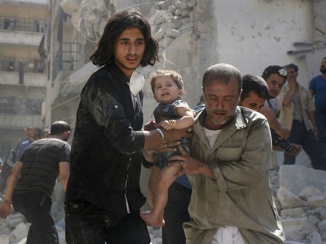 SYRIA, ALEPPO : A Syrian civil defence member and a volunteer carry a little girl rescued from under the rubble of destroyed buildings following a reported airstrike on the rebel-held Salihin neighbourhood of the northern city of Aleppo, on September 10, 2016. The Syrian opposition on September 10 cautiously welcomed …