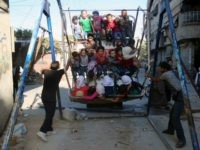 Syrian children ride an attraction in the Syrian rebel-held town of Arbin, in the eastern Ghouta region on the outskirts of the capital Damascus, as they celebrate the Muslim Eid al-Adha holiday on September 13, 2016, the day after an internally backed ceasefire for Syria came into effect as part …