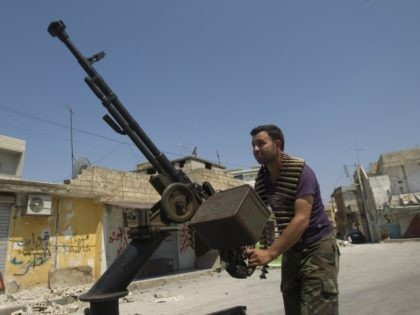 A Syrian rebel fighter loads an anti-aircraft machinegun in the northern town of Atareb, 25 kms east of Syria's second largest city Aleppo, on July 31, 2012. While fighting raged in Syria's commercial capital Aleppo for a fourth straight day, clashes between the Syrian army and rebels also erupted in …