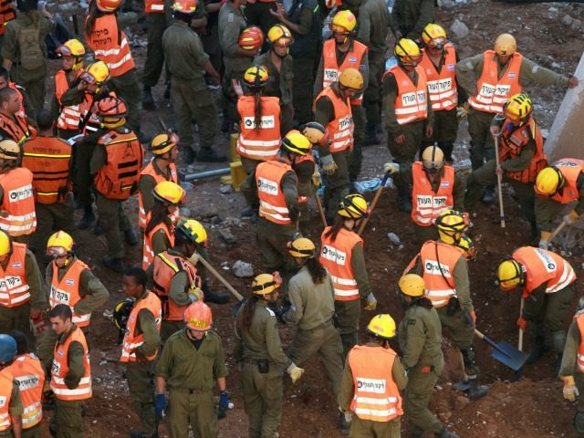 sraeli rescue workers gather at the site where a building collapse on September 5, 2016 in the Ramat Hahayal neighbourhood in the coastal city of Tel Aviv. Two people were killed around 20 others injured, officials said, as rescuers tried to reach several people believed trapped in rubble. / AFP …