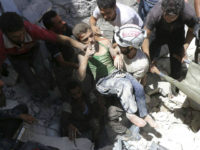 SYRIA, ALEPPO : (FILES) This file photo taken on July 25, 2016 shows Syrian civil defence volunteers, known as the White Helmets, carrying a young boy after they dug him out from under the rubble of buildings destroyed following reported air strikes on the rebel-held neighbourhood of Al-Mashhad in the …
