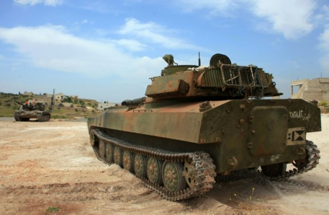 Syrian government tank patrols the town of Khan Tuman, south of Aleppo