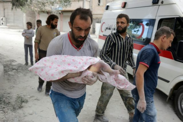 A Syrian man carries the body of an infant retrieved from under the rubble of a building in the al-Muasalat area of the northern Syrian city of Aleppo following a reported airstrike on September 23, 2016