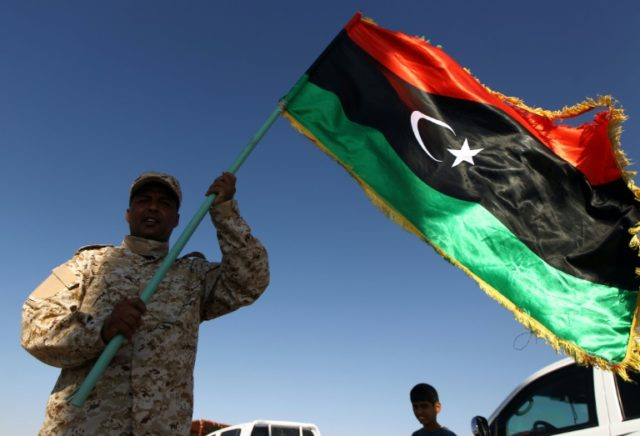 A member of forces opposed to Libya's unity government waves a Libyan flag at the Zueitina oil terminal