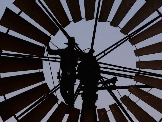 A file photo shows Pineview Station owner Mark Lacey repairing one of his broken windmills on October 25, 2002 in Broken Hill, New South Wales, Australia. An Australian Federal Government report has found that Australian coastal cities and tourist destinations are facing a much higher risk of the destructive effect …