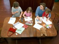 Andrea Farrier sits at her kitchen table with her children Rachel, 8, left, Rebecca, 4, center, and Sarah, 2, as they do schoolwork in their home, Friday, Feb. 20, 2009, in Kalona, Iowa.