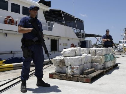 Coast Guard crew members from the cutter Bernard C. Webber stand guard next to bales of cocaine, Friday, April 26, 2013 at the U.S. Coast Guard base in Miami Beach, Fla. The 2,200 pounds of cocaine, worth an estimated $27 million, was seized after stopping a fishing boat in the …