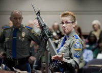 FILE - In this Jan. 28, 2013, file photo, firearms training unit Detective Barbara J. Mattson, of the Connecticut State Police, holds up a Bushmaster AR-15 rifle, the same make and model of gun used by Adam Lanza in the Sandy Hook School shooting, during a hearing of a legislative …