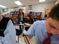 In this Tuesday, Nov. 17, 2015 photo, teacher Nicoleen Winklarek works with students in a seventh grade accelerated math class at Holy Spirit School in East Greenbush, N.Y. The Diocese of Albany, New York, announced recently that it will reduce the frequency of the Common Core-aligned tests while sticking with …