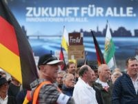 "DRESDEN, GERMANY - JULY 27: An advertising billboard reads: ""Future for all"" behind supporters of the Pegida movement listening to speakers during their weekly gathering on July 27, 2015 in Dresden, Germany. A Pegida leader spoke out against any form of violence against refugees yet called for a radical change …"