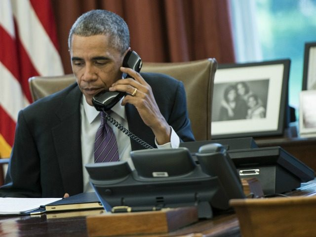 President Barack Obama speaks on the phone in the Oval Office of the White House October 8, 2014 in Washington, DC. Obama participated in a conference call to discuss the US response to the current Ebola outbreak. AFP PHOTO/Brendan SMIALOWSKI (Photo credit should read