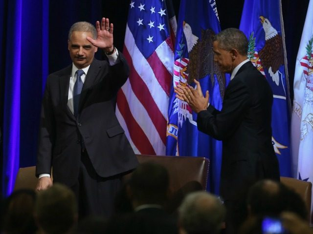Eric Holder waves while applauded by colleagues and US President Barack Obama (R) during his portrait unveiling ceremony at the Justice Department February 27, 2015 in Washington, DC.