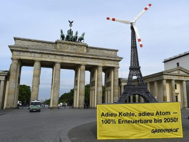 A mockup of the Eiffel tower with symbolic vanes of a windmill on its pinnacle stands in front of the Brandenburg Gate at Pariser Platz in Berlin on May 19, 2015 during a protest of Greenpeace activists. The demonstration took place on the sidelines of the Petersberg Climate Dialogue, an …