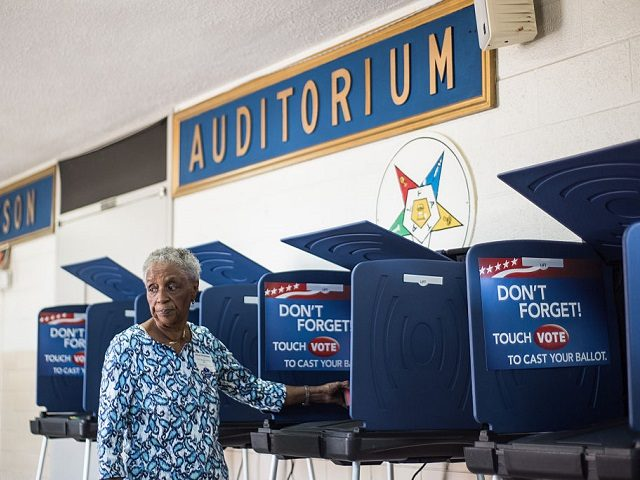 COLUMBIA, SC - FEBRUARY 27: Poll worker Mary Ellison prepares a voting machine at the Prince Hall Masonic Lodge during the South Carolina Democratic Presidential Primary February 27, 2016 in Columbia, South Carolina. Voters in 12 states and one U.S. territory will participate in Super Tuesday on March 1. (Photo …