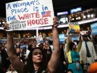 A delegate holds up a sign that reads 'A Woman's Place is in The White House' on the third day of the Democratic National Convention at the Wells Fargo Center, July 27, 2016 in Philadelphia, Pennsylvania. Democratic presidential candidate Hillary Clinton received the number of votes needed to secure the party's nomination. An estimated 50,000 people are expected in Philadelphia, including hundreds of protesters and members of the media. The four-day Democratic National Convention kicked off July 25. (Photo by