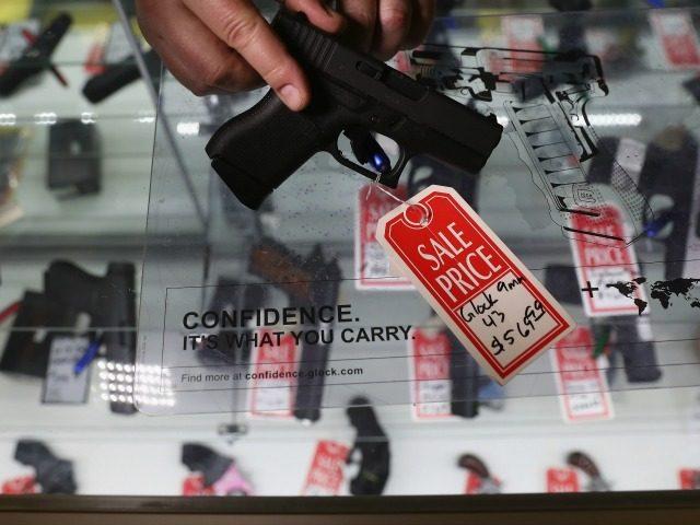 Gun shop owner Jeff Binkley displays a Glock 9mm pistol at Sarge's Sidearms on September 29, 2016 in Benson, Arizona.