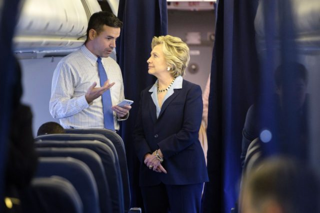 Democratic presidential nominee Hillary Clinton looks at a smart phone with national press secretary Brian Fallon on her plane at Westchester County Airport October 3, 2016 in White Plains, New York. / AFP / Brendan Smialowski (Photo credit should read BRENDAN SMIALOWSKI/AFP/Getty Images)