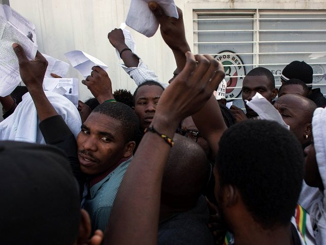 Haitian and African migrants seeking for asylum in the United States, push for a spot as they line up outside a Mexican Migration office, on October 3, 2016, in Tijuana, northwestern Mexico. / AFP / GUILLERMO ARIAS        (Photo credit should read GUILLERMO ARIAS/AFP/Getty Images)