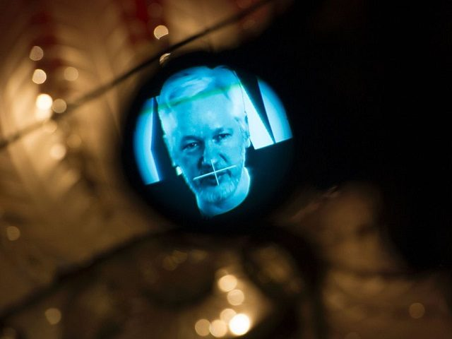 Julian Assange, founder of the online leaking platform WikiLeaks, is seen through the eyepeace of a camera as he is displayed on a screen via a live video connection during a press conference on the platform's 10th anniversary on October 4, 2016 in Berlin. WikiLeaks celebrates its 10th birthday defiantly proud as the pioneer of online leaking platforms, while its controversial founder vows to pursue its work despite widespread criticsm. / AFP / STEFFI LOOS        (Photo credit should read STEFFI LOOS/AFP/Getty Images)