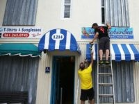 Danny Askins and Brenden Kavana (R) put up hurricane shutters as they prepare the Sandwiches Sea restaurant as Hurricane Matthew approaches the area on October 6, 2016 in Delray Beach, United States.