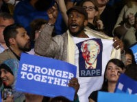 DETROIT, MI - OCTOBER 10: A protester wears a shirt with an image of former U.S. president Bill Clinton and the word 'rape' as democratic presidential nominee former Secretary of State Hillary Clinton speaks during a campaign rally at Wayne State University on October 10, 2016 in Detroit, Michigan. A …