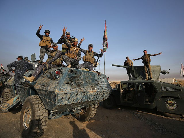Iraqi forces flash the sign for victory as they deploy in the area of al-Shourah, some 45 kms south of Mosul, as they advance towards the city to retake it from the Islamic State (IS) group jihadists, on October 17, 2016. Iraqi Prime Minister Haider al-Abadi announced earlier in the day that the long-awaited operation to recapture Mosul was under way. / AFP / AHMAD AL-RUBAYE (Photo credit should read AHMAD AL-RUBAYE/AFP/Getty Images)