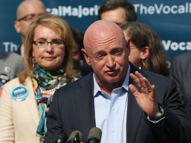 Gun violence victim and former U.S. Congresswoman Gabby Giffords watches her husband, NASA astronaut Mark Kelly, speak as they visits City Hall on her 2016 Vocal Majority Tour on October 17, 2016 in New York City.
