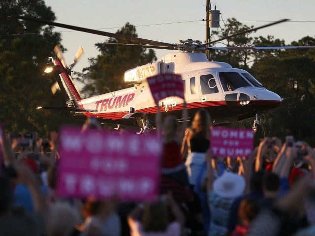 People watch as the helicopter carrying Republican presidential candidate Donald Trump leaves after a campaign rally at the Collier County Fairgrounds on October 23, 2016 in Naples, Florida. Early voting in Florida in the presidential election begins October 24. (Photo by )