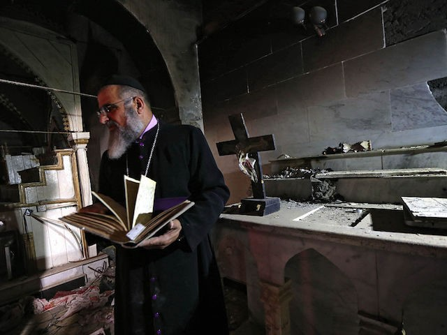 TOPSHOT - David Dosha, the priest of the Church of Mart Shmony, located in the Christian Iraqi town of Bartella, about 15 kilometres (10 miles) east of Mosul, inspects the damage on October 24, 2016 at the church's compound after Iraqi forces retook control of the town from jihadists of …