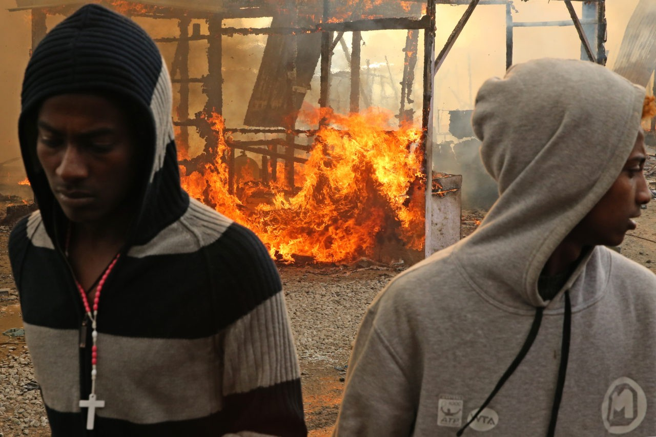 "Migrants walk past burning makeshift shelters during fires at the ""Jungle"" migrant camp in Calais, northern France, on October 26, 2016, during a massive operation to clear the squalid settlement where 6,000-8,000 people have been living in dire conditions. Fresh fires broke out on October 26 in the ""Jungle"" migrant camp on the second day of operations to dismantle the squalid settlement in northern France. Smoke billowed over the sprawling camp near Calais for a second day amid fears that abandoned gas cylinders could explode. / AFP / François NASCIMBENI (Photo credit should read FRANCOIS NASCIMBENI/AFP/Getty Images)"