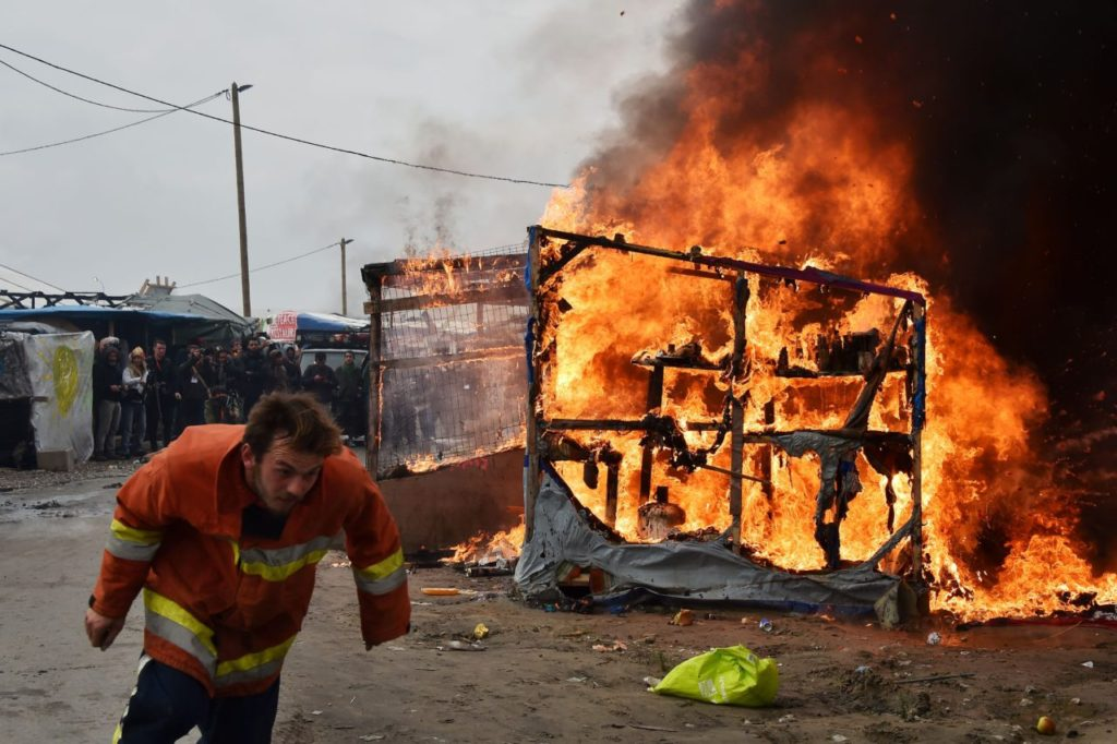 "A member of the demolition crew runs next to a makeshift shelter on fire at the ""Jungle"" migrant camp in Calais, northern France, on October 26, 2016 during a massive operation to clear the squalid settlement where 6,000-8,000 people have been living in dire conditions. Fresh fires broke out on October 26, 2016 in the ""Jungle"" camp on the second day of operations to tear down the squalid settlement in northern France, sending migrants fleeing with their meagre belongings. Huge clouds of black smoke billowed over the sprawling camp near Calais where up to 4,000 migrants remain as authorities continue to evacuate residents and dismantle their makeshift dwellings. / AFP / PHILIPPE HUGUEN (Photo credit should read PHILIPPE HUGUEN/AFP/Getty Images)"