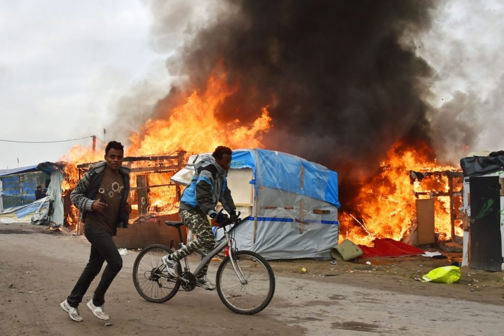 "A migrant cycles as another one cycles next to him as makeshift shelters are on fire at the ""Jungle"" migrant camp in Calais, northern France, on October 26, 2016 during a massive operation to clear the squalid settlement where 6,000-8,000 people have been living in dire conditions. Fresh fires broke out on October 26, 2016 in the ""Jungle"" camp on the second day of operations to tear down the squalid settlement in northern France, sending migrants fleeing with their meagre belongings. Huge clouds of black smoke billowed over the sprawling camp near Calais where up to 4,000 migrants remain as authorities continue to evacuate residents and dismantle their makeshift dwellings. / AFP / PHILIPPE HUGUEN (Photo credit should read PHILIPPE HUGUEN/AFP/Getty Images)"