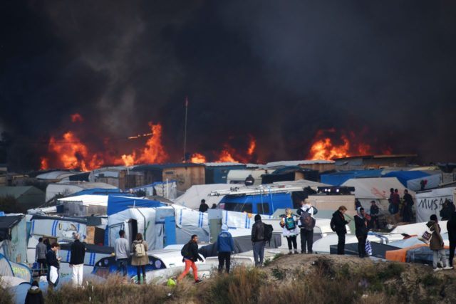 "People watch as smoke rises from fires at the ""Jungle"" migrant camp in Calais, northern France, on October 26, 2016, during a massive operation to clear the squalid settlement where 6,000-8,000 people have been living in dire conditions. Fresh fires broke out on October 26 in the ""Jungle"" camp on …"