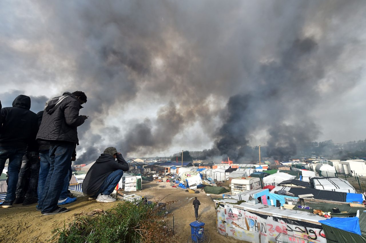 "Migrants look at smoke rising over makeshift shelters on fire at the ""Jungle"" migrant camp in Calais, northern France, on October 26, 2016 during a massive operation to clear the squalid settlement where 6,000-8,000 people have been living in dire conditions. Fresh fires broke out on October 26, 2016 in the ""Jungle"" camp on the second day of operations to tear down the squalid settlement in northern France, sending migrants fleeing with their meagre belongings. Huge clouds of black smoke billowed over the sprawling camp near Calais where up to 4,000 migrants remain as authorities continue to evacuate residents and dismantle their makeshift dwellings. / AFP / PHILIPPE HUGUEN (Photo credit should read PHILIPPE HUGUEN/AFP/Getty Images)"