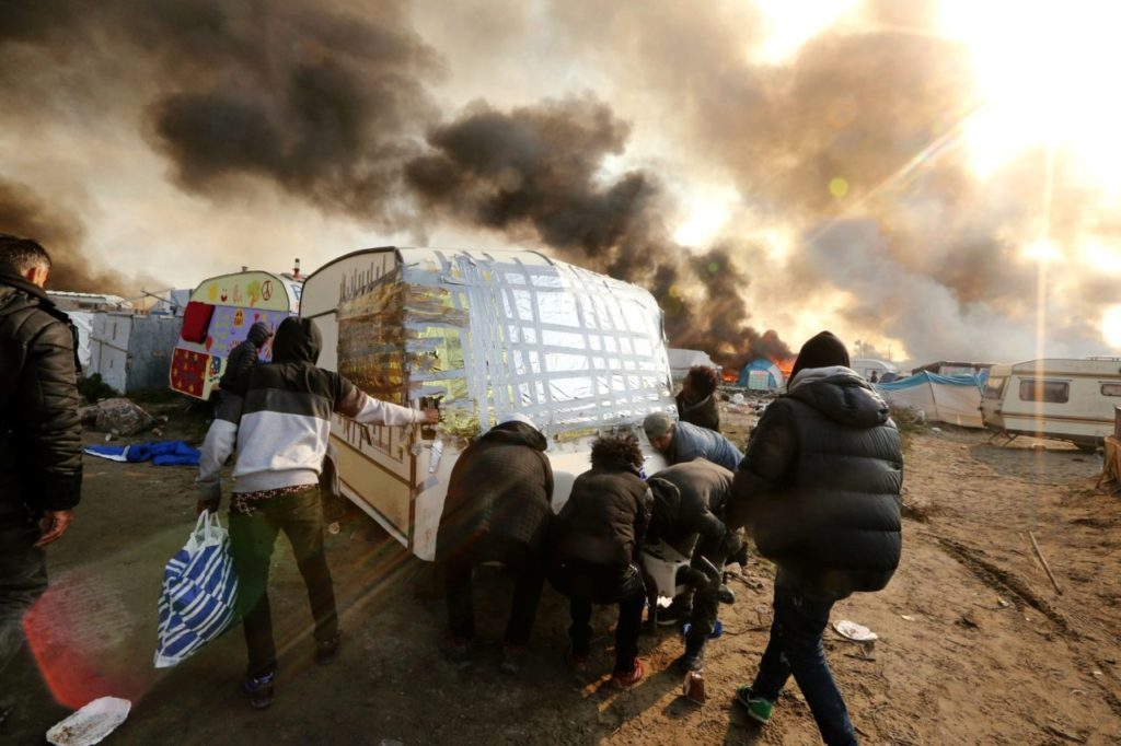 "People try to move a caravan as smoke rises from fires at the ""Jungle"" migrant camp in Calais, northern France, on October 26, 2016, during a massive operation to clear the squalid settlement where 6,000-8,000 people have been living in dire conditions. Fresh fires broke out on October 26 in the ""Jungle"" camp on the second day of operations to tear down the squalid settlement in northern France, sending migrants fleeing with their meagre belongings. Huge clouds of black smoke billowed over the sprawling camp near Calais where up to 4,000 migrants remain as authorities continue to evacuate residents and dismantle their makeshift dwellings. / AFP / François NASCIMBENI (Photo credit should read FRANCOIS NASCIMBENI/AFP/Getty Images)"