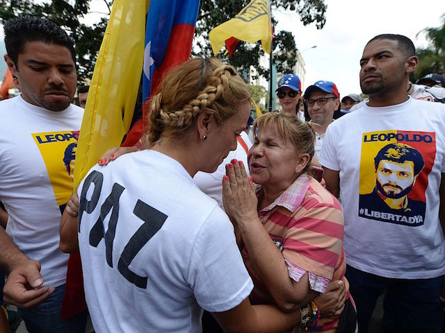 "Lilian Tintori (2-L), wife of prominent jailed opposition leader Leopoldo Lopez, listens to a woman during a march against the government of Venezuelan President Nicolas Maduro in the streets of Caracas on October 26, 2016. Venezuela's political rivals are set to engage in a volatile test of strength on Wednesday, with the opposition vowing mass street protests as President Nicolas Maduro resists efforts to drive him from power. The socialist president and center-right-dominated opposition accuse each other of mounting a ""coup"" in a volatile country rich in oil but short of food. / AFP / Federico PARRA (Photo credit should read FEDERICO PARRA/AFP/Getty Images)"