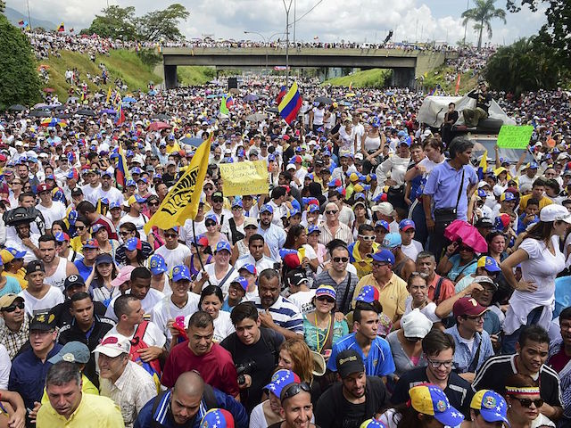 People demonstrate against the government of Venezuelan President Nicolas Maduro in Caracas on October 26, 2016. Opponents of Maduro rallied in the streets as the leftist leader convened a crisis security meeting resisting their efforts to drive him from power. Thousands of opposition supporters began to gather at seven points around Caracas in the morning planning to march and join up in the east of the capital. / AFP / Ronaldo SCHEMIDT (Photo credit should read RONALDO SCHEMIDT/AFP/Getty Images)