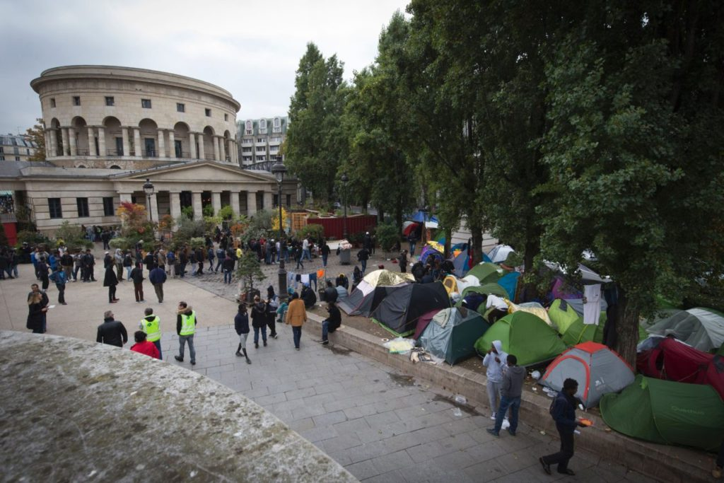 Migrants stand near tents in a street of Paris on October 28, 2016 where migrants live in squalid conditions in one of the camps sprouting up around the French capital.  More than one million people fleeing war and poverty in the Middle East, Asia and Africa poured into Europe last year, sowing divisions across the 28-nation bloc and fuelling the rise of far-right movements, including Germany's Pegida and France's National Front.  / AFP / JOEL SAGET        (Photo credit should read JOEL SAGET/AFP/Getty Images)
