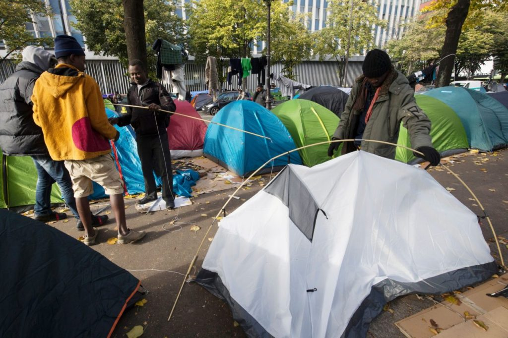 Migrants set a tent in a street of Paris on October 28, 2016 where migrants live in squalid conditions in one of the camps sprouting up around the French capital.  More than one million people fleeing war and poverty in the Middle East, Asia and Africa poured into Europe last year, sowing divisions across the 28-nation bloc and fuelling the rise of far-right movements, including Germany's Pegida and France's National Front.  / AFP / JOEL SAGET        (Photo credit should read JOEL SAGET/AFP/Getty Images)