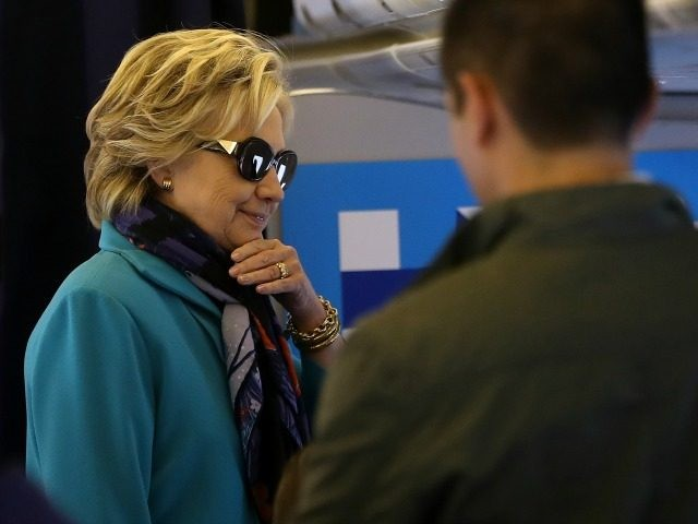 Democratic presidential nominee former Secretary of State Hillary Clinton talks with members of her staff aboard her campaign plane at Westchester County Airport on October 29, 2016 in White Plains, New York.