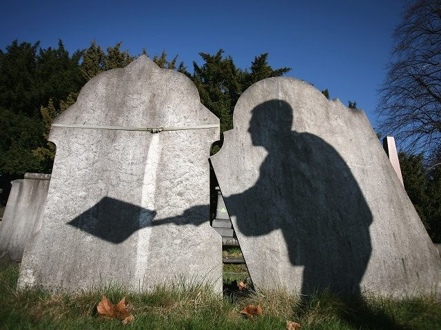 LONDON, ENGLAND - MARCH 02: The shadow of a cemetery worker is cast on reclaimed gravestones in London City Cemetery on March 2, 2009 in London, England. The cemetery is piloting a scheme whereby graves over 75 years old become eligible for reclamation. New interments will be placed into the …
