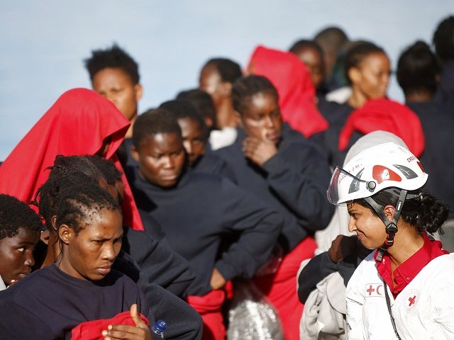 This handout picture taken and released by the Italian Red Cross on October 22, 2016 shows migrants landing in Vibo Marina, after a rescue operation in the Mediterranean Sea. Nine people drowned, ten were missing and nearly 1000 migrants were rescued off the Libyan coast on October 22, with over …