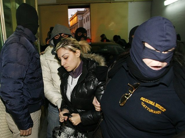 An unidentified woman si escorted after being arrested with Mafia boss Giovanni Nicchi (not pictured) on December 5, 2009 in Palermo. Nicchi is considered to be the number three of Palermo's cosa nostra mafia. AFP PHOTO / Marcello PATERNOSTRO (Photo credit should read MARCELLO PATERNOSTRO/AFP/Getty Images)