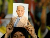 A Lebanese Hezbollah supporter holds a picture of the militant group's Christian ally, Free Patriotic Movement leader Michel Aoun, during a rally in southern Beirut on May 25, 2009 to mark the ninth anniversary of Israel's withdrawal from southern Lebanon after a 22-year occupation. Lebanon is preparing to hold parliamentary …