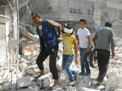 Syrians walk over rubble following air strikes on the rebel-held Fardous neighbourhood of the northern embattled Syrian city of Aleppo on October 12, 2016. / AFP / AMEER ALHALBI (Photo credit should read AMEER ALHALBI/AFP/Getty Images)